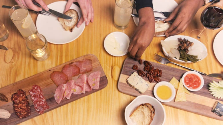 Photo of people's hands eating from a table of charcuterie and other foods