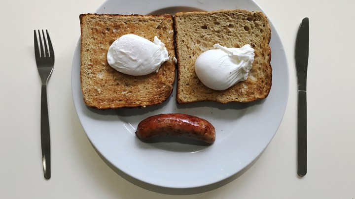 Two pieces of toast on a white plate with poached eggs and piece of toast, resembling a sad face.